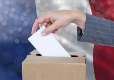 Χέρι που βάζει την ψηφοφορία της Γαλλίας στο κάλπη με το λαμπιρίζοντας ελαφρύ υπόβαθρο bokeh Στοκ Εικόνες