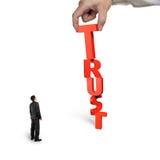 Χέρι που βάζει το Τ για τη λέξη εμπιστοσύνης με το μικρό κοίταγμα επιχειρηματιών Στοκ φωτογραφίες με δικαίωμα ελεύθερης χρήσης