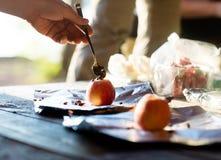 Χέρι που γεμίζει τα τσιπ σοκολάτας στη Apple Στοκ Εικόνες