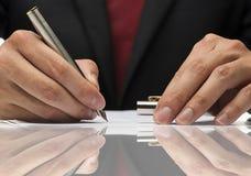 Χέρι που γράφει ένα έγγραφο με την αντανάκλαση Στοκ Εικόνες