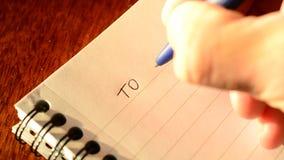 Χέρι που γράφει ΓΙΑ ΝΑ ΚΑΝΕΙ τον κατάλογο με μια μάνδρα στο σημειωματάριο φιλμ μικρού μήκους
