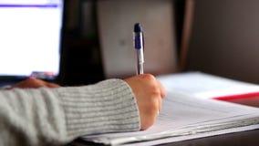 Χέρι που γράφει, που ελέγχει και που υπογράφει τα έγγραφα ή τη μελέτη σπουδαστών απόθεμα βίντεο