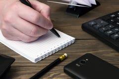 Χέρι που γράφει σε ένα σημειωματάριο, ένα τηλέφωνο και έναν υπολογιστή Στοκ Φωτογραφίες