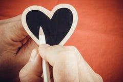 Χέρι που γράφει στην ξύλινη καρδιά για την ημέρα του βαλεντίνου Στοκ Εικόνα