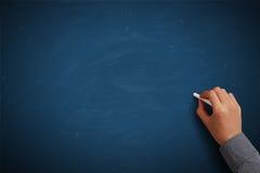 Χέρι που γράφει στον κενό μπλε πίνακα κιμωλίας στοκ φωτογραφία με δικαίωμα ελεύθερης χρήσης