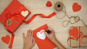 Χέρι που γράφει σ' αγαπώ τη φράση στη ευχετήρια κάρτα που βρίσκεται στον πίνακα με τα κιβώτια δώρων απόθεμα βίντεο