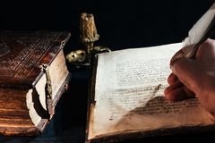 Χέρι που γράφει την παλαιά Βίβλο βιβλίων με ένα παλαιό χειρόγραφο φτερών Στοκ Εικόνα