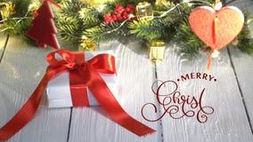 Χέρι που γράφει το άσπρο γράφοντας κείμενο καλλιγραφίας ζωτικότητας Χαρούμενα Χριστούγεννας στο άσπρο ξύλινο υπόβαθρο με τα δώρα  απόθεμα βίντεο