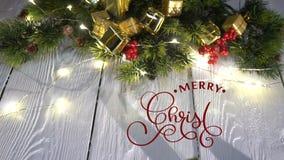 Χέρι που γράφει το άσπρο γράφοντας κείμενο καλλιγραφίας ζωτικότητας Χαρούμενα Χριστούγεννας στο άσπρο ξύλινο υπόβαθρο με τα δώρα  φιλμ μικρού μήκους