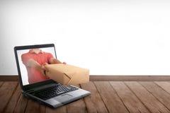Χέρι που δίνει ένα κιβώτιο από την οθόνη lap-top στοκ εικόνα