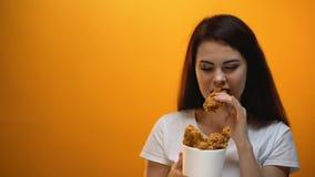 Χέρι που δίνει το τηγανισμένο κοτόπουλο στο κορίτσι, παραγωγή κοινωνίας accustoms στο άχρηστο φαγητό απόθεμα βίντεο