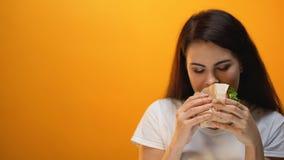 Χέρι που δίνει το χάμπουργκερ στο νέο κορίτσι, παραγωγή κοινωνίας accustoms στο άχρηστο φαγητό απόθεμα βίντεο