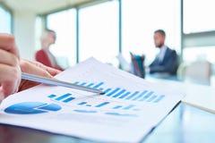 Χέρι που δείχνει στη γραφική παράσταση στατιστικών Στοκ Εικόνα