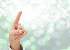 Χέρι που δείχνει με το λαμπιρίζοντας ελαφρύ υπόβαθρο bokeh Στοκ Φωτογραφία