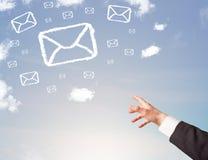 Χέρι που δείχνει στα σύννεφα συμβόλων ταχυδρομείου στο μπλε ουρανό Στοκ Εικόνες