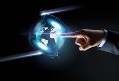 Χέρι που δείχνει το δάχτυλο την εικονική γήινη προβολή Στοκ Εικόνα