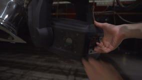 Χέρι που εγκαθιστά τη λάμπα φωτός αλόγονου στο στάδιο που ανάβει τον επαγγελματικό εξοπλισμό απόθεμα βίντεο