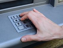 Χέρι που εισάγει τους αριθμούς στη μηχανή του ATM στοκ εικόνα