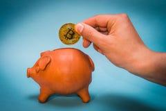 Χέρι που εισάγει bitcoin το νόμισμα στην παλαιά piggy τράπεζα Στοκ Εικόνες