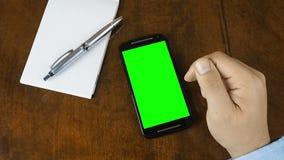 Χέρι που λειτουργεί στην πράσινη οθόνη γραφείων smartphone φιλμ μικρού μήκους