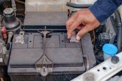 Χέρι που ελέγχει και που επισκευάζει την μπαταρία αυτοκινήτων στοκ εικόνα