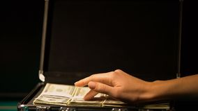 Χέρι που ελέγχει τα χρήματα στη βαλίτσα, έννοια δωροδοκίας, κάλυψη-επάνω στην παράνομη επιχείρηση φιλμ μικρού μήκους