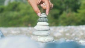 Χέρι που κάνει την ισορροπία πετρών την εν πλω παραλία Πνευματική έννοια αρμονίας φιλμ μικρού μήκους
