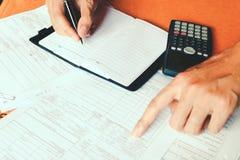 Χέρι που κάνει τις σημειώσεις σε ένα σημειωματάριο με μια μάνδρα και που χρησιμοποιεί το μετρώντας ασβέστιο Στοκ φωτογραφία με δικαίωμα ελεύθερης χρήσης