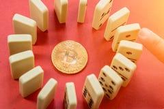 Χέρι που καταστρέφει τη σειρά κύκλων των ντόμινο με το χρυσό bitcoin στο κέντρο Στοκ Εικόνες