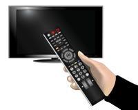 Χέρι που κρατά έναν τηλεχειρισμό μπροστά από την τηλεόραση Στοκ εικόνα με δικαίωμα ελεύθερης χρήσης