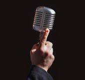 Χέρι που κρατά ένα αναδρομικό μικρόφωνο πέρα από το μαύρο υπόβαθρο Στοκ Φωτογραφίες