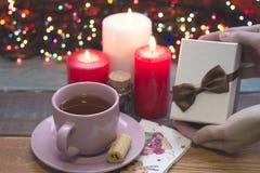 Χέρι που κρατά ένα κιβώτιο δώρων, ένα φλυτζάνι του τσαγιού, καίγοντας κεριά Στοκ φωτογραφίες με δικαίωμα ελεύθερης χρήσης