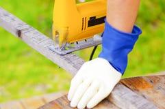 Χέρι που κρατά ένα κομμάτι του ξύλου ενώ το ηλεκτρικό τορνευτικό πριόνι το κόβει Στοκ φωτογραφία με δικαίωμα ελεύθερης χρήσης