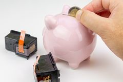 Χέρι που κρατά ένα νόμισμα δίπλα σε piggy τράπεζα και δύο κασέτες μελανιού Κόστος της έννοιας μελανιού στοκ εικόνες