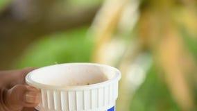 Χέρι που κρατά ένα πλαστικό φλυτζάνι με τον καπνό από τα μουτζουρωμένα δέντρα υποβάθρου θερμότητας απόθεμα βίντεο
