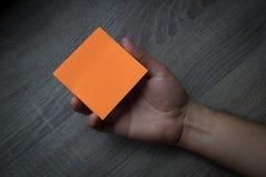 Χέρι που κρατά ένα πορτοκαλί έγγραφο σημειώσεων - επιχειρησιακή έννοια Στοκ φωτογραφίες με δικαίωμα ελεύθερης χρήσης