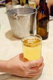 Χέρι που κρατά ένα ποτήρι της μπύρας σε έναν πίνακα στοκ φωτογραφία