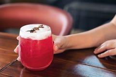 Χέρι που κρατά ένα ποτήρι της σόδας φραουλών στον ξύλινο πίνακα στοκ φωτογραφία