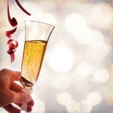 Χέρι που κρατά ένα ποτήρι του λαμπιρίζοντας άσπρων κρασιού και των κορδελλών Στοκ Εικόνες