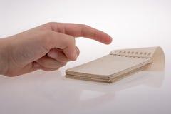 Χέρι που κρατά ένα σημειωματάριο Στοκ Φωτογραφία