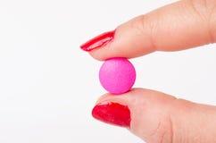 Χέρι που κρατά ένα χάπι μεταξύ των δάχτυλων φαρμακείο ιατρική φαρμάκων απομονωμένος Στοκ φωτογραφία με δικαίωμα ελεύθερης χρήσης
