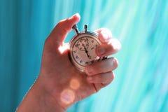 Χέρι που κρατά ένα χρονόμετρο με διακόπτη και που πιέζει το κουμπί για να σημειώσει το χρόνο Φλόγα ακτίνων ήλιων Στοκ Εικόνα