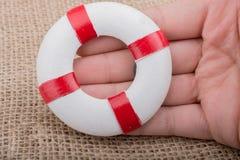 Χέρι που κρατά ένα Lifesaver στο ύφασμα Στοκ εικόνα με δικαίωμα ελεύθερης χρήσης
