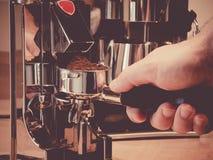 Χέρι που κρατά ένα portafilter κάτω από το μύλο espresso Στοκ φωτογραφίες με δικαίωμα ελεύθερης χρήσης