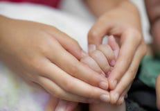 Χέρι που κρατά μια ακραία κινηματογράφηση σε πρώτο πλάνο χεριών μωρών Στοκ φωτογραφία με δικαίωμα ελεύθερης χρήσης