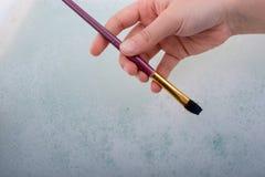 Χέρι που κρατά μια βούρτσα χρωμάτων στο νερό με τον αφρό Στοκ εικόνες με δικαίωμα ελεύθερης χρήσης