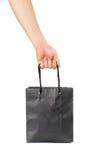 Χέρι που κρατά μια κενή μαύρη τσάντα αγορών Στοκ εικόνα με δικαίωμα ελεύθερης χρήσης