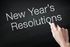 Χέρι που κρατά μια κιμωλία και που γράφει το νέο ψήφισμα έτους στοκ φωτογραφία