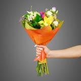Χέρι που κρατά μια όμορφη ανθοδέσμη των διαφορετικών λουλουδιών απομονωμένος στοκ εικόνα με δικαίωμα ελεύθερης χρήσης
