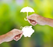 Χέρι που κρατά μια piggy τράπεζα και μια ομπρέλα εγγράφου στοκ εικόνες